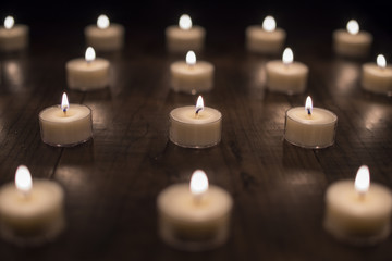 Lit Tea Light Candles on a Wooden Table (Center Focus)