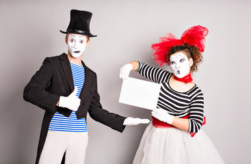 Two mimes with a sign for advertising