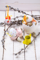 Decorative Easter eggs in bucket, willow  branches  and rabbit o