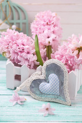 Hyacinths flowers in wooden box and decorative heart on turquois