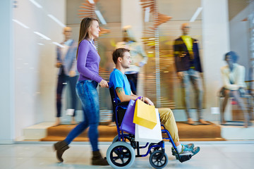 Pretty girl shopping with her disable boyfriend in wheelchair