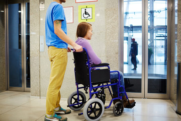 Guy and his girlfriend in wheelchair waiting for elevator