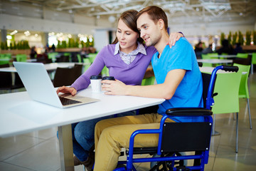 Amorous girl embracing her boyfriend in wheelchair while networking in cafe