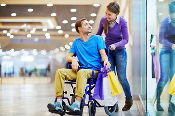 Caring girl talking to her boyfriend in wheelchair during sale