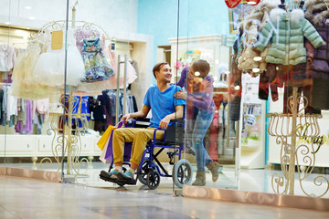 Caring girl and her disable boyfriend visiting clothing department in the mall
