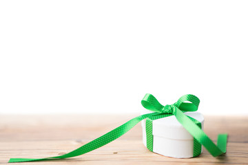 Gift box with green ribbon on wooden floor isolated on white