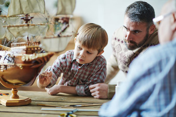 Adorable youngster painting toy ship with his father and grandfather near by