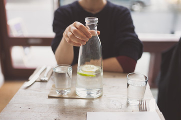 Young woman drinking water at table