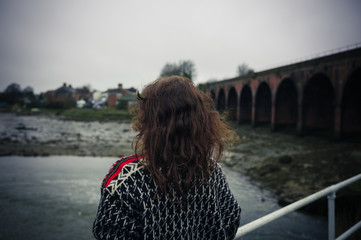 Young woman standing alone on bridge