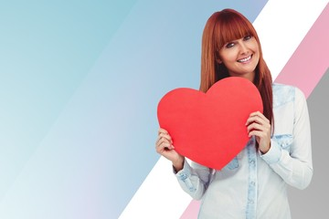 Composite image of attractive hipster woman behind a red heart