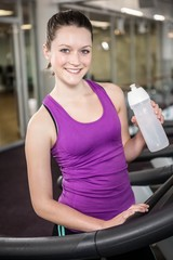 Smiling woman holding bottle of water