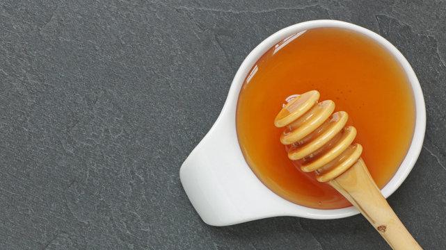 Miel et cuillère à miel en bois sur ardoise