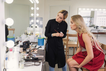 she evaluates her makeup in the mirror after a stylist