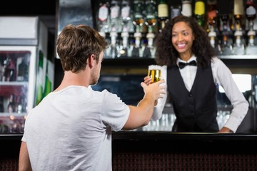 Barmaid serving beer to man