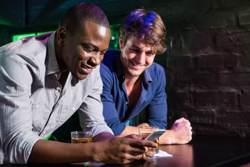Two men looking at mobile phone and smiling at bar counter