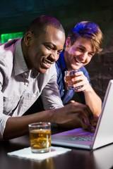 Two men having whiskey and using laptop at bar counter
