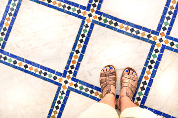 Feet selfie from upper view of a woman traveler in sandal during a tour trip around the world. Souvenir photo of multicolor museum floor made of small tiles. Tourist take a photo of her own leg.