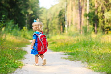 cute little girl with backpack in summer forest