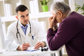 Young doctor carefully listening patient about his pains