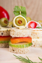 finger foods with bread, peppers, cucumber, cheese and olives