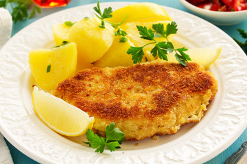 Baked chicken breast with a crispy crust, served with boiled potatoes.