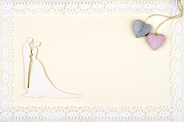 Bride and groom silhouette on retro paper framed with lace. Two wooden hearts in corner.