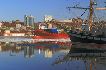 the reflection in the sea surface sailing vessel and buildings in the city of Vladivostok