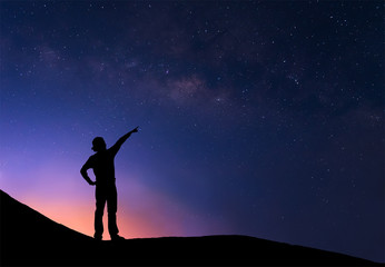 Sillhouette of woman standing next to the milky way and pointing