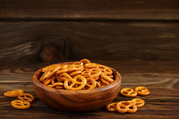 Bretzel pretzels with salt on a wooden background.
