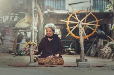 Old women demonstrate to procedure of making Thai Silk weaving