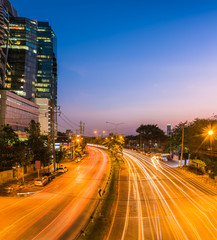 night scene of modern city. Building and light trail on road wit