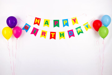 colorful garlands, streamer, party hats and confetti. festive decoration background with sample text Happy Birthday