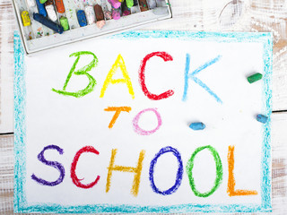 words BACK TO SCHOOL written in blue crayon on paper