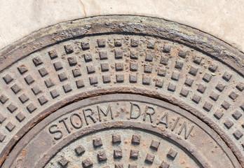 Industrial outdoor metal storm drain cover in beige concrete