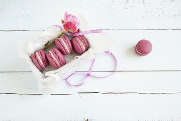 Sweet crimson french macaroons and rose with box on  light dyed wooden background