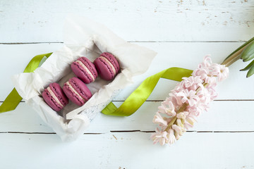 Sweet crimson french macaroons with box and mint on  light dyed wooden background