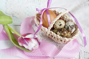 Easter eggs with ribbons in a wicker basket, next to the pink tulip.
