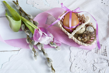 Easter eggs with ribbons in a wicker basket, next to the pussy willow and tulip.