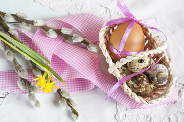 Easter eggs with ribbons in a wicker basket, next to the pussy willow and daffodil (yellow narcissus)