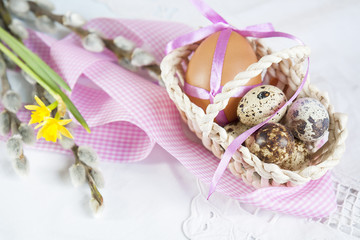 Easter eggs with ribbons in a wicker basket, next to the pussy willow and daffodil (yellow narcissus).