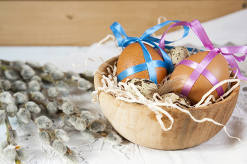 Easter eggs with ribbons in a wooden bowl, next to the willow seals on light background