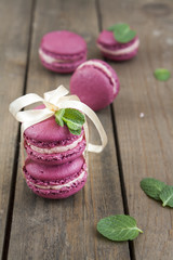 Sweet crimson french macaroons tied with ribbon on dark wooden background