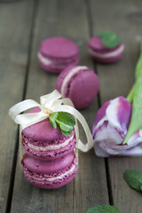 Sweet crimson french macaroons tied with ribbon and tulip on dark wooden background