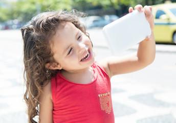 Kind im roten Shirt macht Selfie mit dem Handy