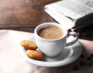 Cup of coffee, cookie and newspaper on wooden table background
