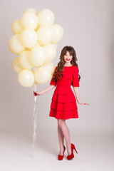 Young woman with balloons on a white background