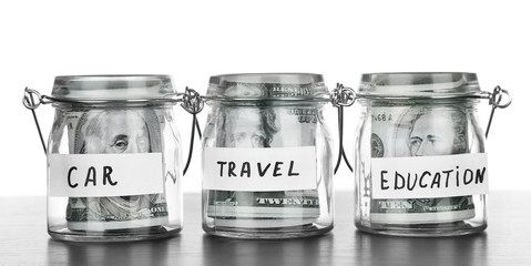 Three jars for different needs full of banknotes