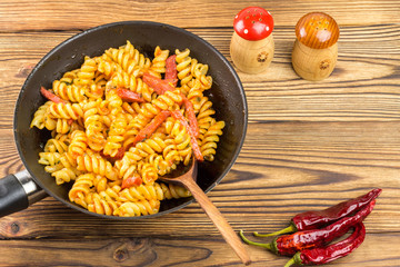 Italian pasta fusilli with tomato sauce and sausage in pan, wooden spoon, red pepper on table, top view, space for text