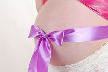 belly of pregnant woman tied with purple bow