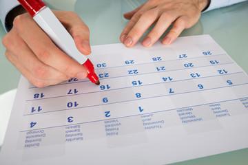 Fototapete - Businessman Highlighting Date On Calendar